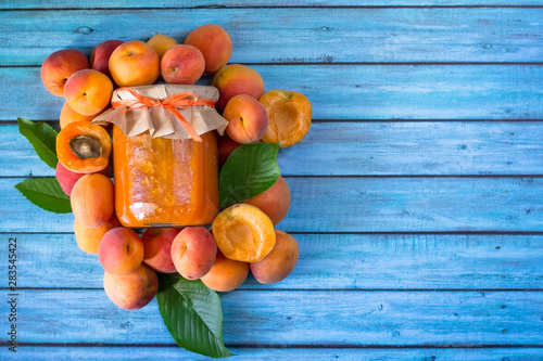 Organic homemade apricot jam on vibrant  blue wooden table. Healthy prepared food. Copy space. - 283545422