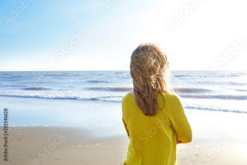 Fotografia  Woman standing lonely on the beach and looking at the sea