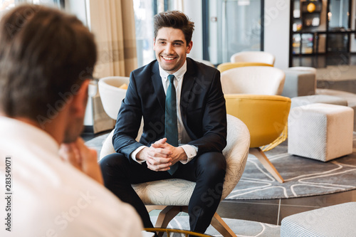 Fotografia  Happy businessmen colleagues indoors in business center office talking with each other