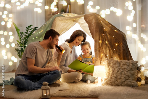 Obraz family, hygge and people concept - happy mother, father and little daughter reading book with torch light in kids tent at night at home - fototapety do salonu