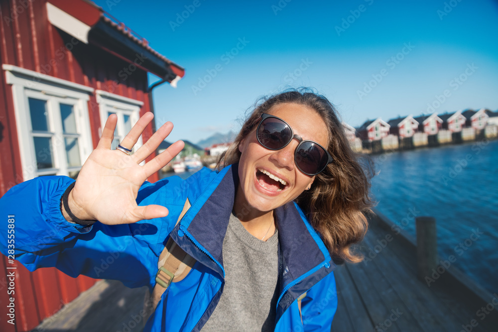 Fototapety, obrazy: Beautiful young happy smiling girl traveler on the background of traditional red rorbu traveling to Lofoten Norway