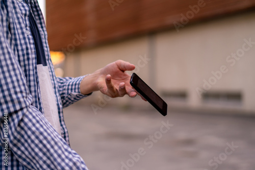 Obraz person holding a smartphone in the street, a phone falling and flying  down by an accident - fototapety do salonu