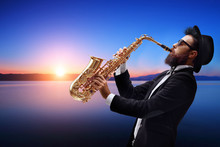 Male Jazz Musician Playing A Saxophone With A Sunset And Water