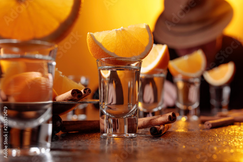 Foto auf Leinwand Alkohol Glasses of gold tequila with orange and cinnamon sticks on a table in bar.