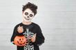 Leinwanddruck Bild Happy Halloween.funny child in a skeleton costume with halloween pumpkin