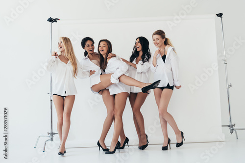 Foto auf Leinwand Texturen full length view of sexy multiethnic feminists wearing heels and white shirts laughing on white