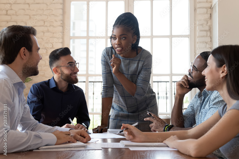 Fototapeta Female black executive talking to diverse employees at office briefing