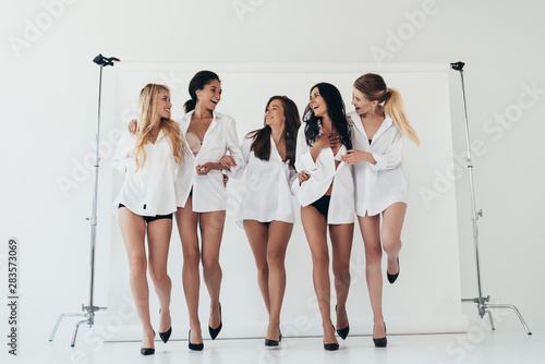 obraz PCV full length view of five sexy multiethnic girls wearing white shirts and heels smiling on grey