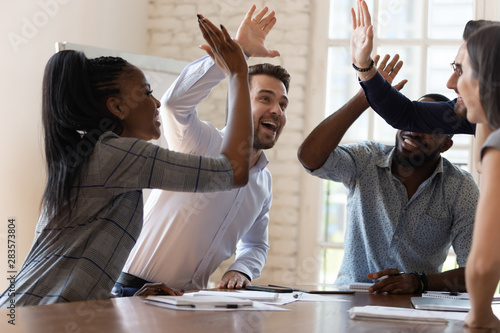 Fotografía  Multiracial euphoric business team people give high five in office