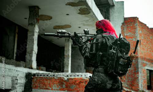 Fotomural  Airsoft red-hair woman in uniform with machine gun standing on knee