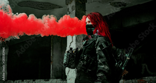 Fotografía  Airsoft red-hair woman in uniform with red smoke in hand