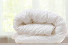 A Folded White Duvet Lies On A Table On A Blurred Background.
