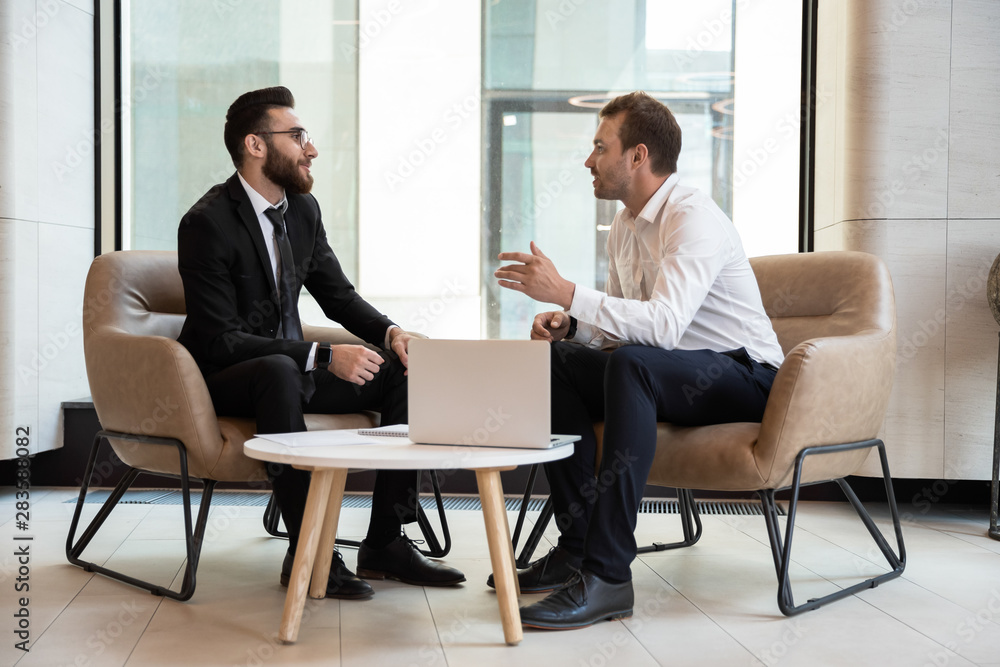 Fototapeta Confident businessmen discussing deal at meeting in modern office