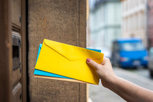 Delivering Letters By Mail Carrier. Postal Worker Inserting Envelope Into Mail Slot