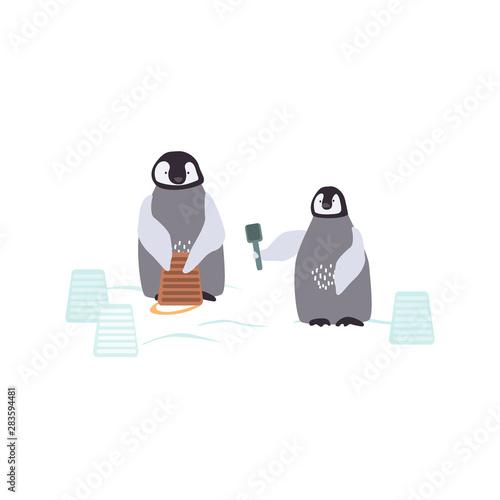 Obraz na plátně Two cartoon penguins are bulding a snowcastle