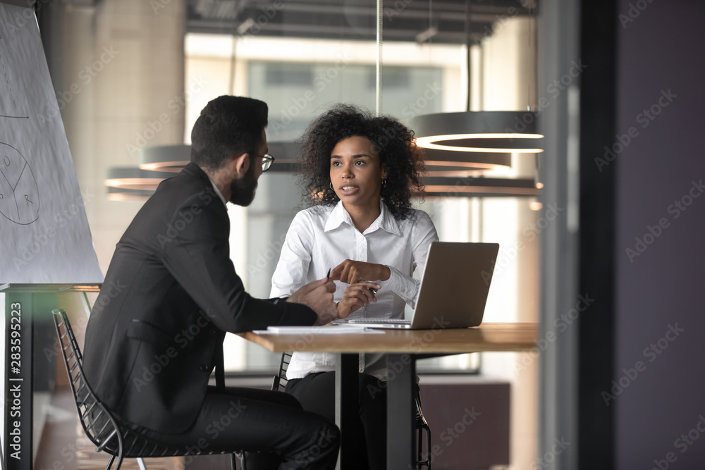 Fototapeta African American businesswoman consulting client in boardroom