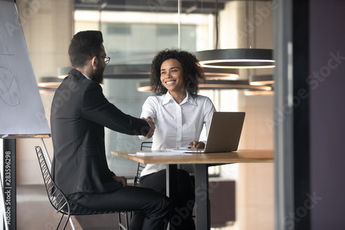 Photo Smiling African American businesswoman shaking hand of business partner
