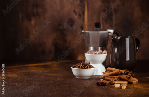 Fotografie, Obraz  Coffee pot with spices on brown background.