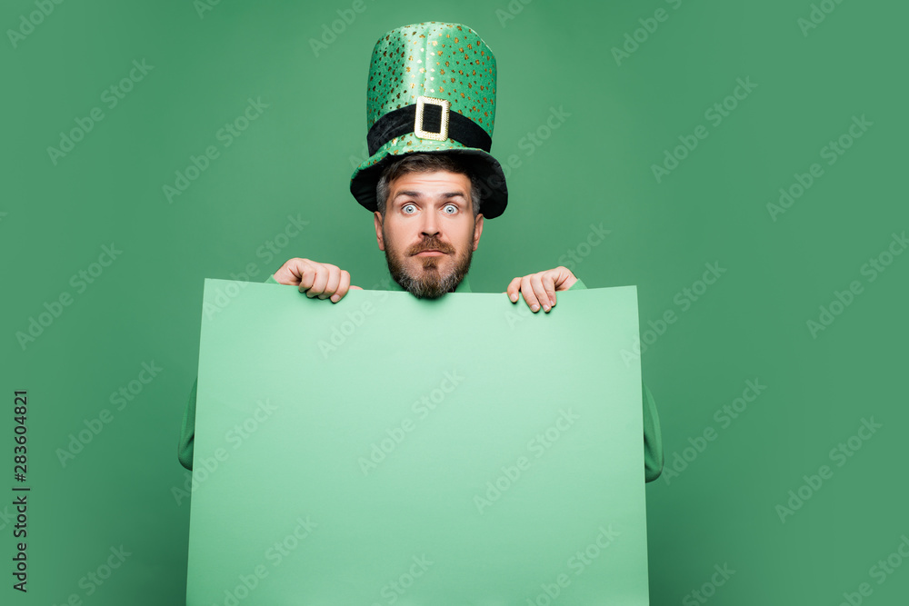Fototapeta Shocked and happy male face. Happy Saint Patrick's day. Hipster in leprechaun hat and costume with wide open eyes celebrating Saint Patrick's day.
