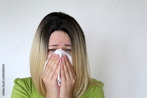 Sick woman sneezing and blowing her nose in a handkerchief Tablou Canvas