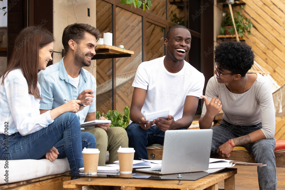 Fototapeta Smiling diverse millennial friends have fun studying in cafe