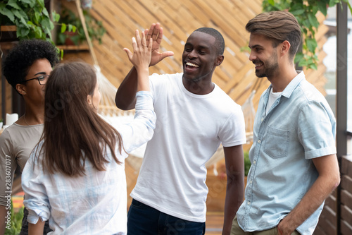 Obraz na plátně  Smiling diverse friends give high five greeting at meeting