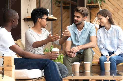 Diverse young people relax in cafe communicating - 283607612