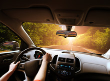 Car Dashboard With Driver's Hands On The Steering Wheel And Rear View Mirrors On A Road With Trees Against Sky With Sunset