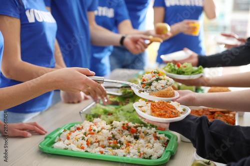 Volunteers serving food to poor people, closeup Canvas Print