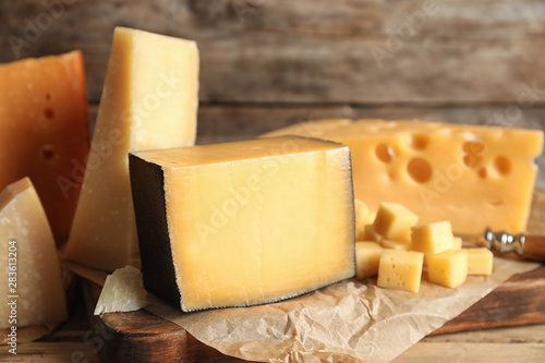 Fototapeta Different types of delicious cheese on table against wooden background obraz
