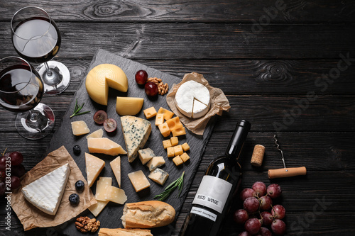 Fototapeta Different types of delicious cheese served on black wooden table, top view obraz