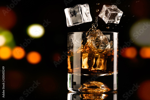 Poster Alcohol glass of whiskey and ice cube