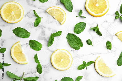 Fresh mint with sliced lemon on white marble background, flat lay