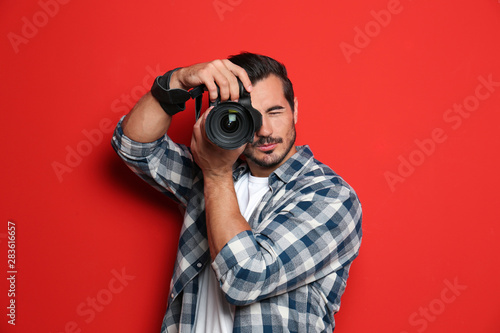 Fotografie, Obraz Young professional photographer taking picture on red background
