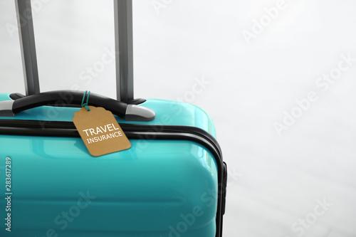 Photo Stylish suitcase with travel insurance label on light background, closeup