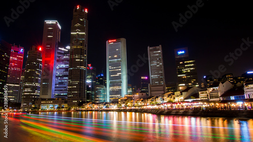 Nightime in Singapore at South Bridge Road showing illimunated buildings and light trail from tourist boats crusing the Singapore river Wallpaper Mural