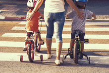 Mother Goes Pedestrian Crossing With Children On Bicycles. A Woman With Son And Daughter Crossing The Road In The City. Back View. Tone