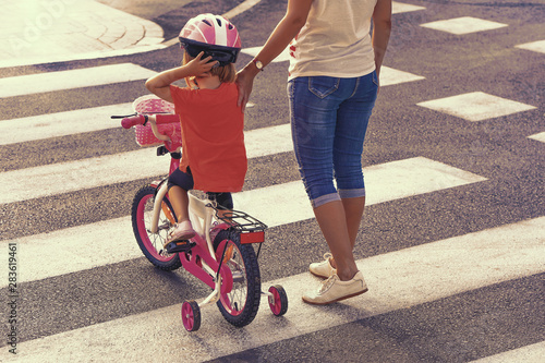 Fényképezés  Mother goes pedestrian crossing with daughter on bicycle
