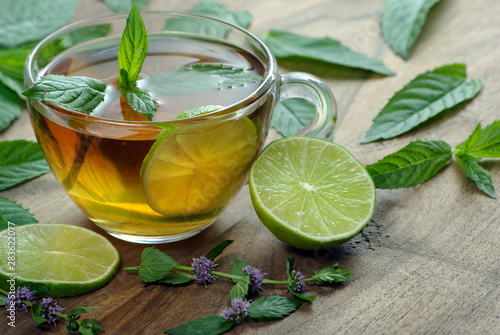 Cafe cup of mint tea and lime on a wooden table. herbal tea