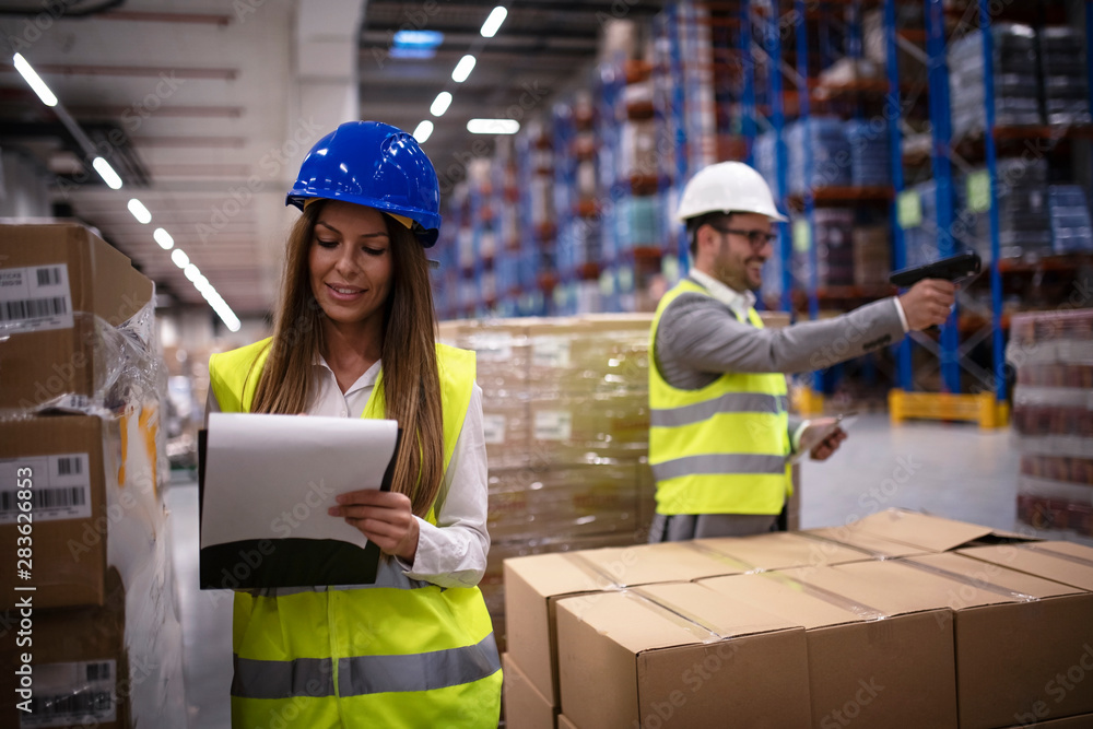 Fototapeta Female factory worker in reflective uniform with hardhat helmet checking new arrival of goods in warehouse while worker using bar code reader in background. Logistics and distribution.