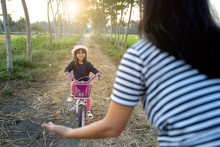 Mother And Daughter Outdoor Together Learning To Ride Bicycle