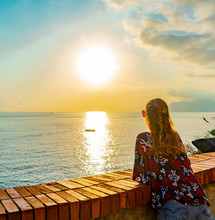 Young Woman Watching The Sunset Over The Mediterranean Sea. Blue Sky And Little Boat.
