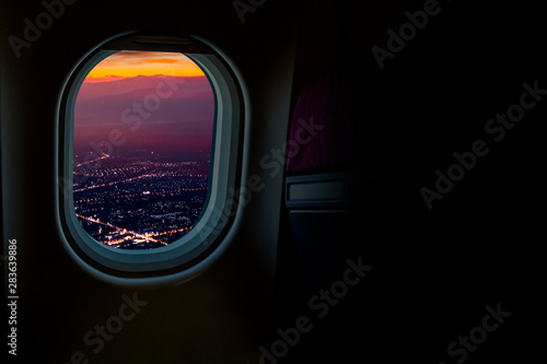 Valokuva  Night cityscapes view from airplane window in the sky with dark copy space for t
