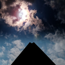 Solar Eclipse Shining Through The Clouds In The Sky Above A Black Pyramid Shaped Building