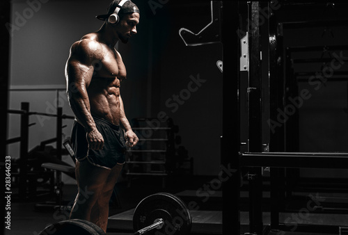 Fototapeta Muscular athletic bodybuilder man hard workout  in gym over dark background with dramatic light with barbell obraz