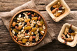 canvas print picture - Healthy trail mix snack made of nuts (walnut, almond, peanut) and dried fruits (raisin, sultana) in wooden bowl, photographed overhead (Selective Focus, Focus on the trail mix in the big bowl)