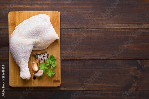 Fototapeta Fresh raw chicken thigh on wooden cutting board with seasoning on the side, phot