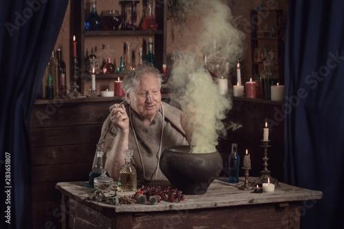 Obraz elderly alchemist monk brews  magic potion - fototapety do salonu