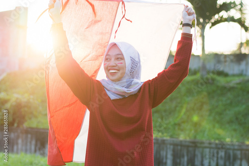 Fotografia  portrait of young asian muslim woman with scarf lift the red and white flag into