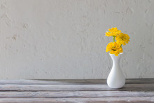 Yellow Zinnia In White Vase On Wooden Table